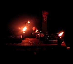 Ron pouring coffee among tiki torches, kerosene lantern, and camp fire